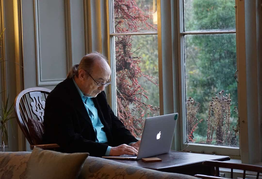 A person using a laptop computer sitting on top of a window